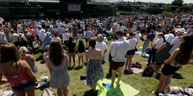 People observe the minute silence for the victims of the shooting in Tunisia last week, at the All England...