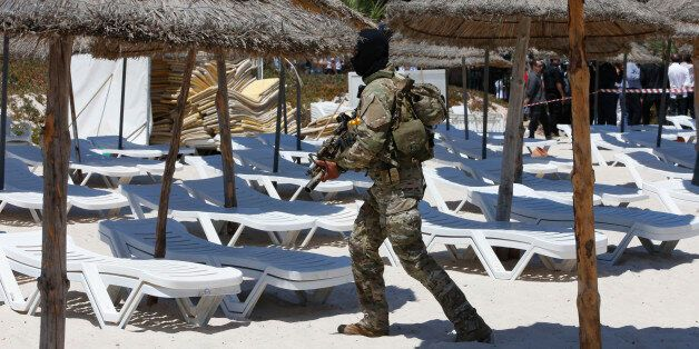 A hooded Tunisian police officer patrols ahead of the visit of top security officials of Britain, France,...