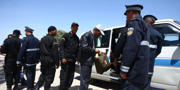 Tunisian security officers check vehicles in the city of Kairouan where ultraconservative Islamic group,...