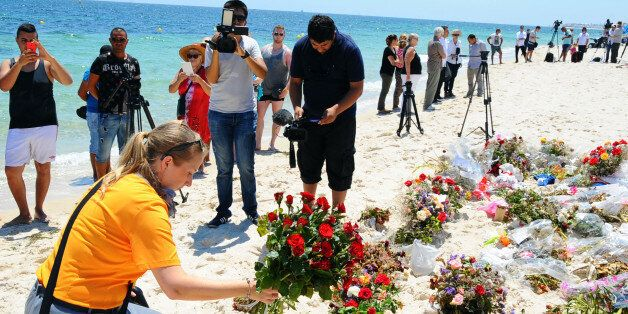 An unidentified tourist lays flowers to honor the victims of a deadly beach attack a week ago that killed...