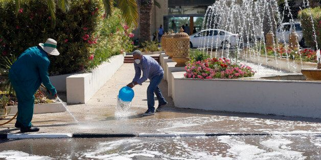 Workers clean a sidewalk in the garden of the Imperial Marhaba hotel where a shooting attack took place...