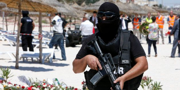 A hooded Tunisian police officer stands guard ahead of the visit of top security officials of Britain,...
