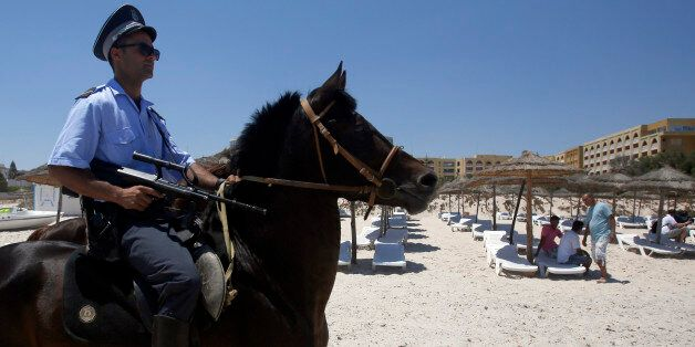 A Tunisian police officer on horse patrol the beach in front of the Imperial Marhaba Hotel in Sousse,...