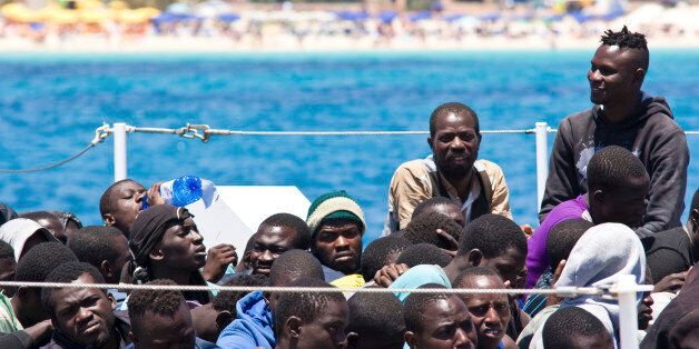 Migrants wait to disembark from a Coast Guard ship that rescued them at sea, in the Island of Lampedusa,...