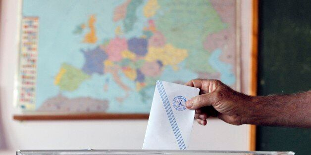 A man casts his vote as the map of Europe is seen in the background at a polling station in Athens, Sunday,...