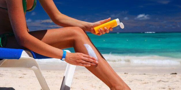 Tan woman applying sun protection