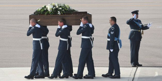 Pallbearers carry a coffin from a British RAF C-17 plane, confirmed as carrying the body of Adrian Evans,...