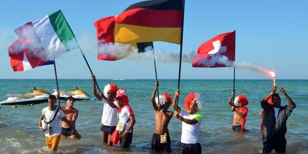 Tourists take part in a gathering in solidarity with Tunisia's tourism industry, on June 29, 2015 on...