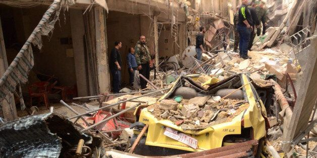 In this photo released by the Syrian official news agency SANA, Syrians gather amid the rubble of damaged...