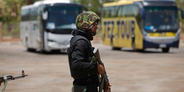 A member of the Egyptian security forces stands guard around tourist buses at the site of a suicide bombing...