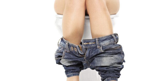 Female seated at a toilet with her pants down isolated on white