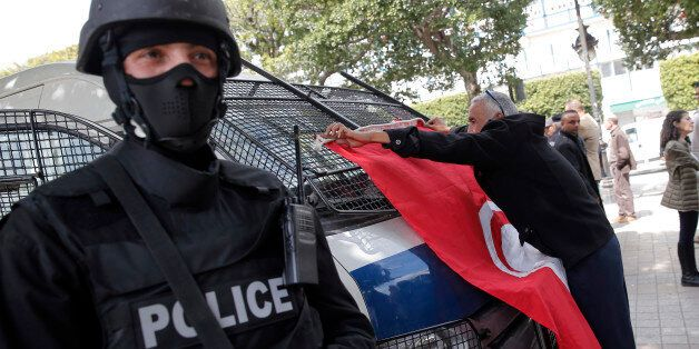 A man places a Tunisian flag onto a police car as a policeman stands guard during a demonstration two...