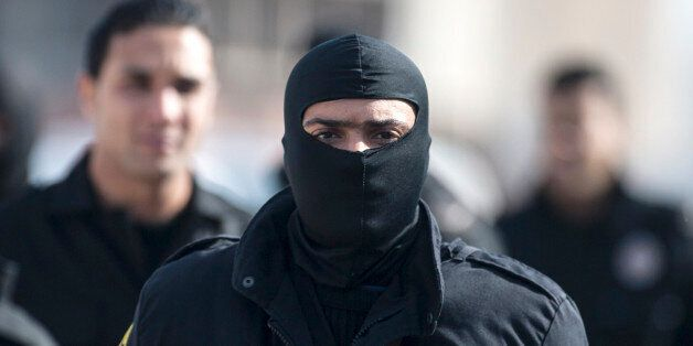 A hooded member of the Tunisian anti-terrorist police forces (BAT) walks near a house where suspected...