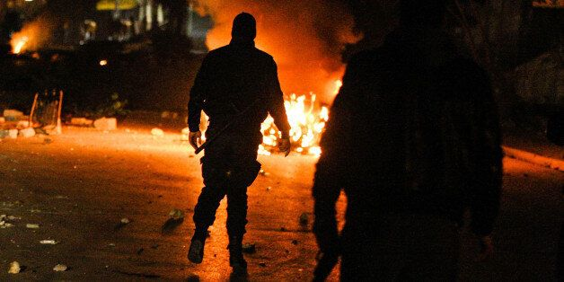 Tunisian Police officers walks in a street during clashes with riot police close to a tax office in Ettadhamen,Tunisia,...