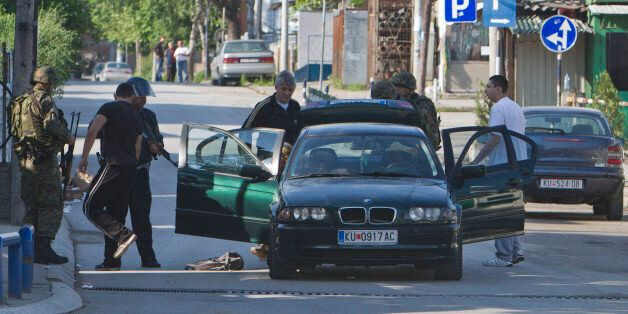 Macedonian special unit members search a vehicle as a fighting between police forces and members of an...