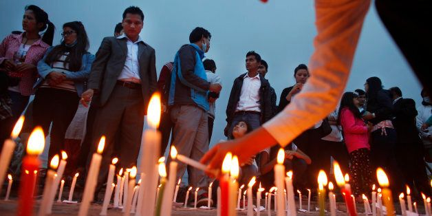 Nepalese participate in a candle light vigil for victims of last week's earthquake in Kathmandu, Nepal,...
