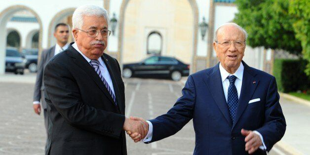 Tunisian President Beji Caid Essebsi, right, shakes hands with his Palestinian counterpart, Mahmoud Abbas,...