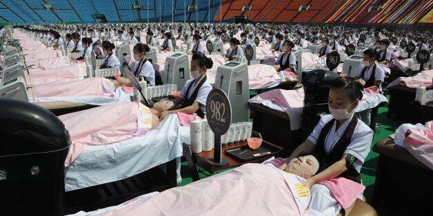 Beauticians apply facial care to women as they lay on beds in a stadium in Jinan, east China's Shandong...