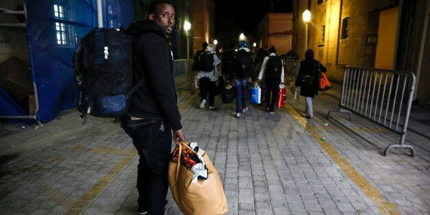 In this Wednesday, April 22, 2015 photo, migrants make their way to accommodate themselves after being...