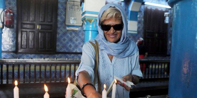 Tunisian Jew Chantal Dabi lights a candle at the Ghriba synagogue in Djerba, south Tunisia, Wednesday,...
