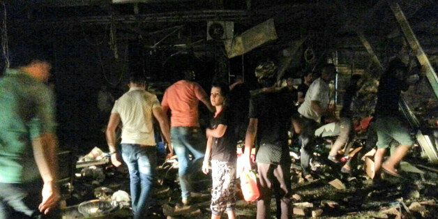Civilians inspect the site of a bomb attack near restaurants and coffee shops filled with customers in...