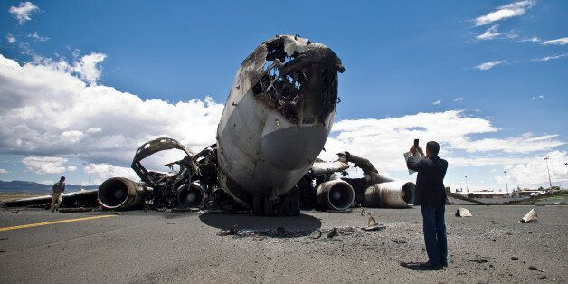 An airport official uses his mobile to take pictures of the wreckage of a military transport aircraft...
