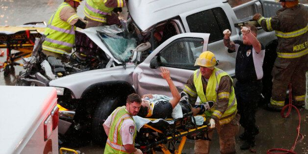 The driver of a truck which crashed during severe weather on Interstate 35 gestures to his rescuers after...