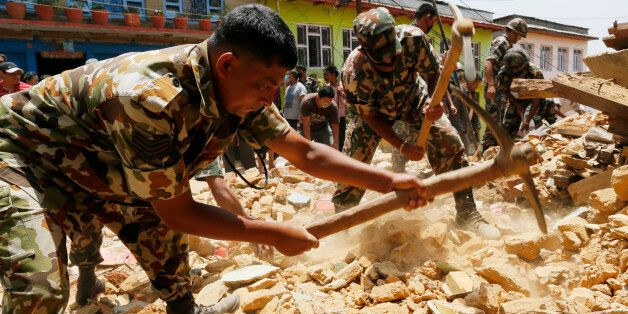 Nepalese soldiers dig for a rumored missing person in the rubble of a collapsed house in the Manakamana...