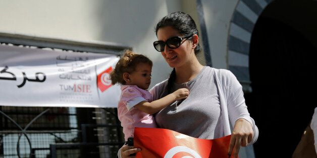 A Tunisian woman who lives in Egypt holds her daughter after she casts her ballot for her country's parliamentary...