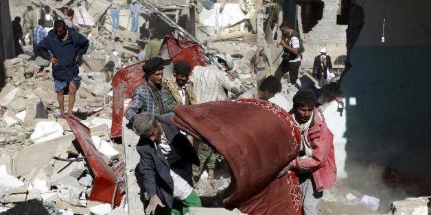 Des Yéménites récupèrent des biens des débris des maisons détruites par les raids aériens conduits par...