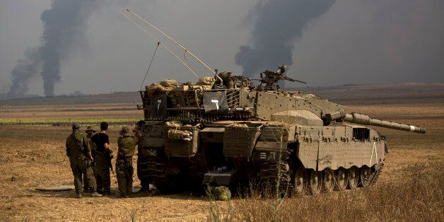 Israeli soldiers stand behind a tank as heavy smoke rises from the Gaza Strip Tuesday, July 22, 2014....