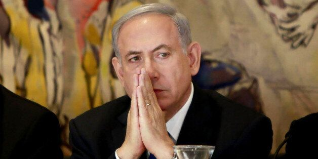 Israel's Prime Minister Benjamin Netanyahu listens during an event following the first session of the...