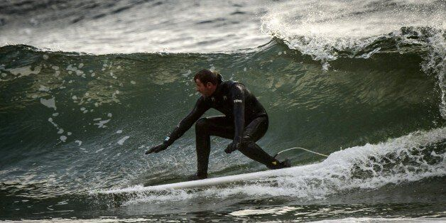 Norwegian Tommy Olsen surfs in Unstad, in the Lofoten Islands within the Arctic Circle, on April 18,...