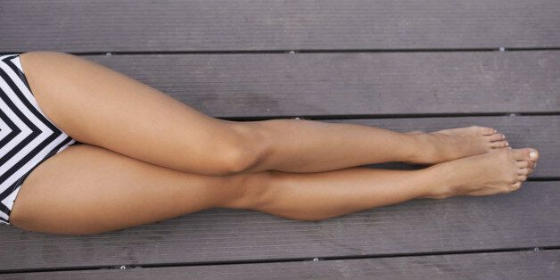 A cropped shot of a woman in a bikini lying next to a clear