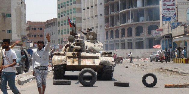 Militiamen loyal to Yemen's President Abed Rabbo Mansour Hadi take positions at a street in Aden, Yemen,...