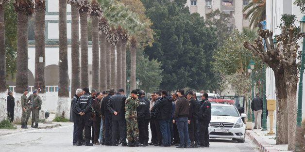 Tunisian police and defense officials gather outside the National Bardo museum in Tunis, Tunisia, Saturday...