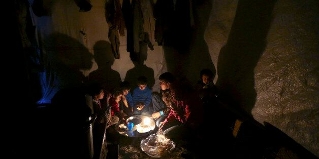 Syrian refugee children sit on the ground inside their tent home as they take their dinner at a Syrian...
