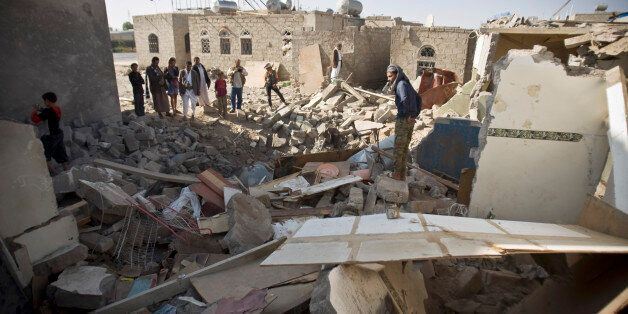 Yemenis gather near the rubble of houses destroyed by Saudi airstrikes near the airport in Sanaa, Yemen,...