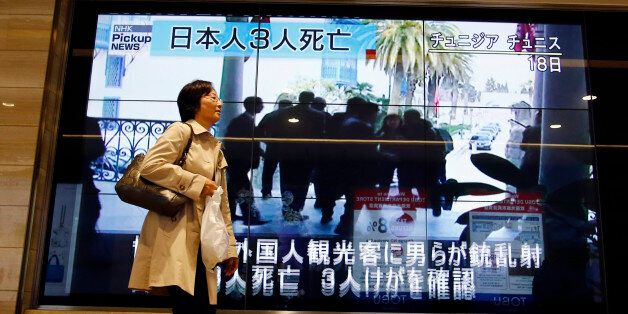 A woman walks past a screen showing TV news reports of the militant attack on tourists in Tunisia, Thursday,...