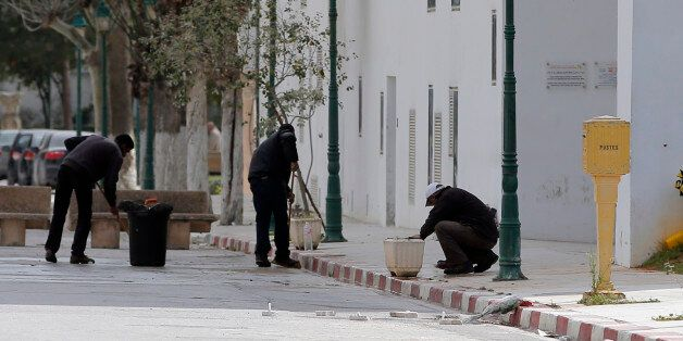 Workers clean the entrance of the National Bardo Museum two days after gunmen attacked the museum and...