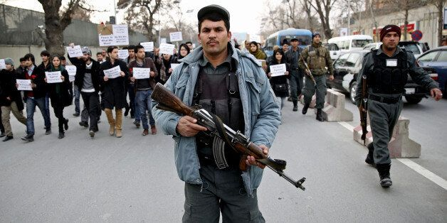 An Afghan police walks ahead of members of civil society organizations for their protection as they march...