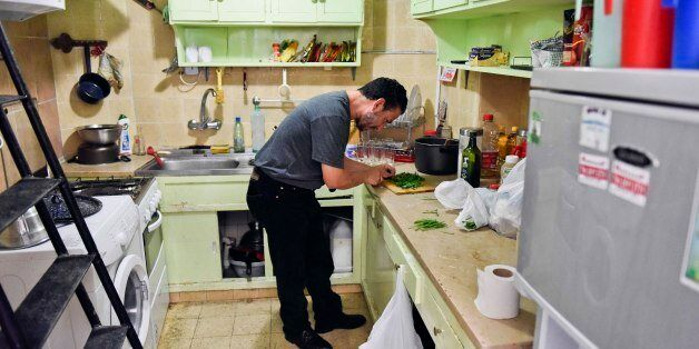 In this Feb. 25, 2015 photo, Adel bin Muhammad El Ouerghi, from Tunisia, chops parsley in the home he...
