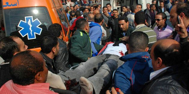 A wounded man is evacuated from the site of an explosion in a crowded area near the Egyptian High Court,...