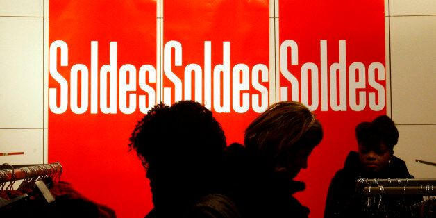 Shoppers look at clothes next to sales posters during the first day of the winter sales in Paris, Wednesday,...