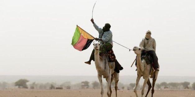 Un touareg brandit le drapeau du Mouvement national de libération de l'Azawad (MNLA) lors d'une manifestation...
