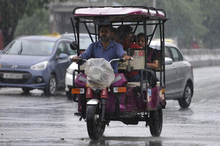 An e-rickshaw and vehicles during rain in Noida.