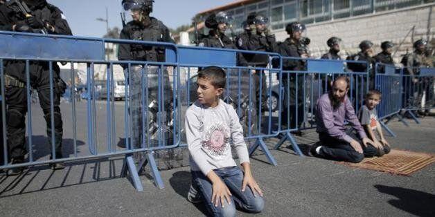 Des Palestiniens prient dans le quartier Ras al-Amoud (banlieue de Jérusalem-Est), sous les yeux de policiers...