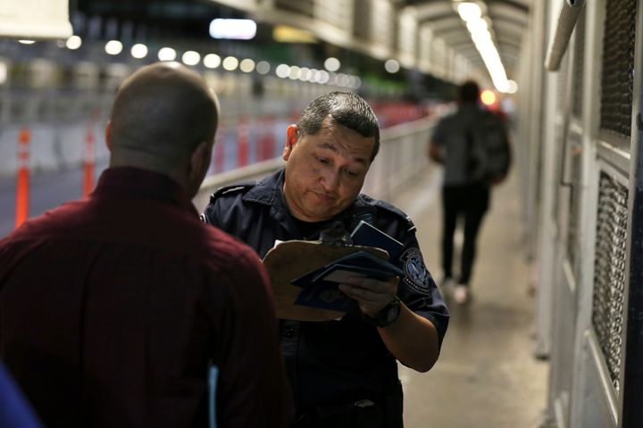 A U.S. Customs and Border Protection officer checks the documents of migrants who are on their way to apply for asylum in the