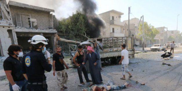 Des civils constatent les dégâts d'une bombe à Alep, le 25