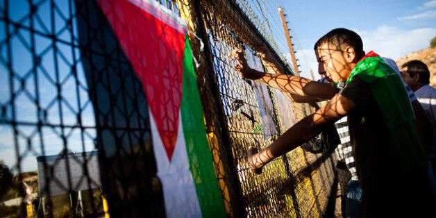 RAMALLAH, WEST BANK - OCTOBER 18: Palestinians look through a fence adorned with flags and posters next...